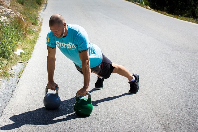 CrossFitter macht Liegestütz auf Kettlebells